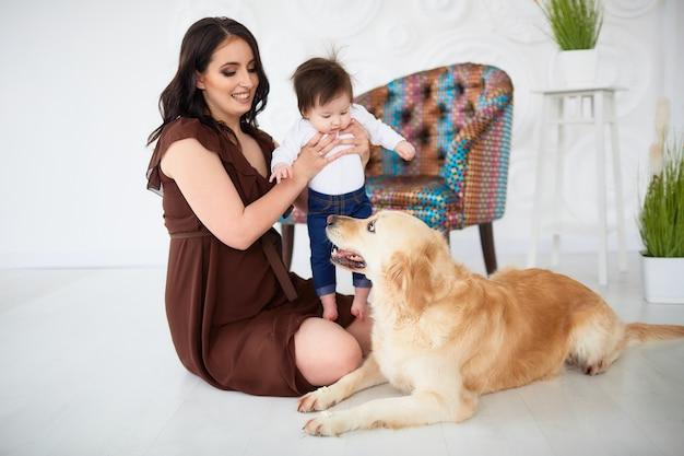 A mãe com a filha sentada no chão e olhando para o cão