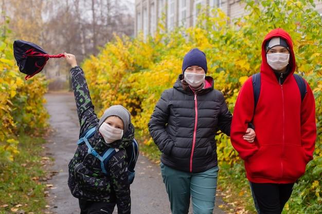 A mãe com dois filhos na rua usando máscaras protetoras, caminhando