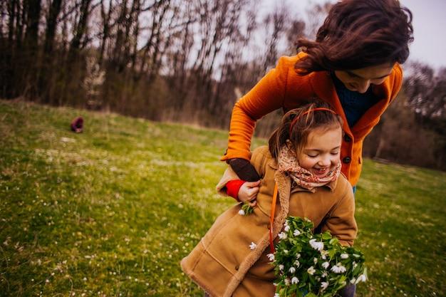 A mãe com filha andando pelo parque