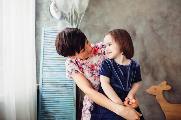 A mãe com filha sentada na escada e mantendo balões