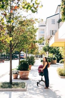 A mãe com um carrinho de bebê fica na rua perto de banheiras com arbustos verdes