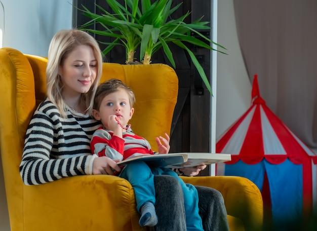A mãe conta uma história para o filho enquanto está sentado na poltrona em casa