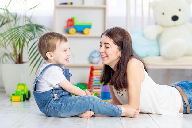 A mãe conversa com o menino ou brinca em casa com brinquedos educativos no quarto das crianças. uma família feliz e amorosa.