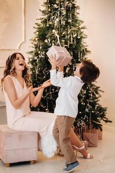 A mãe dá ao filho um presente de natal perto da árvore de natal. família feliz.
