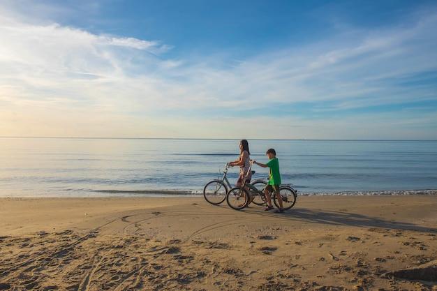 A mãe e a criança montam uma bicicleta na praia felizmente.