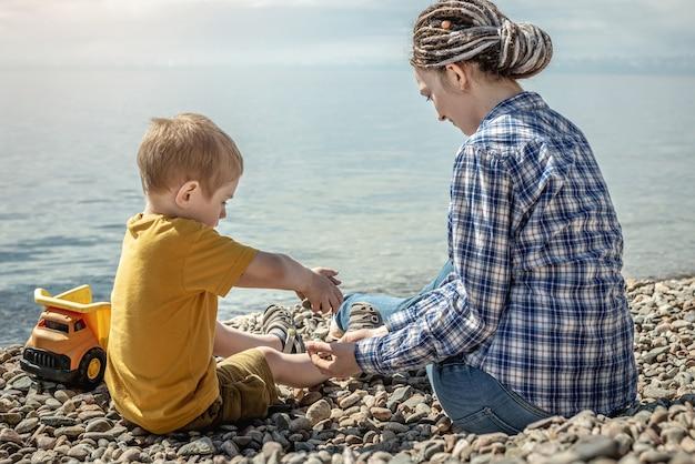 A mãe e a criança na costa pedregosa de um grande lago estão brincando juntas e recolhendo pedras