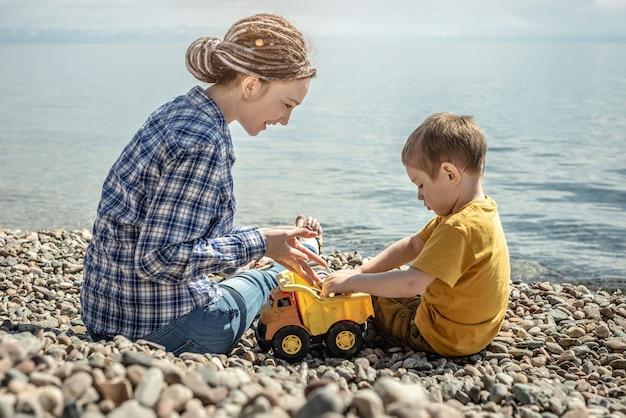 A mãe e a criança na pedregosa costa do mar estão brincando juntas e recolhendo pedras