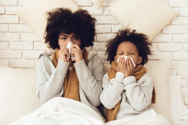 A mãe e a filha africanas doentes estão sentando-se na cama.