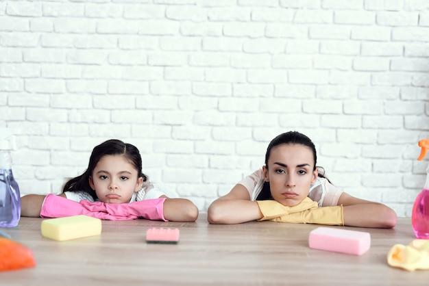 A mãe e a filha cansadas encontram-se na mobília e no descanso.