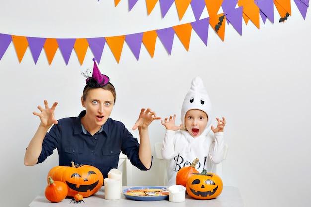 A mãe e a filha dela fazem caretas para comemorar o halloween. fundo branco com bandeiras coloridas