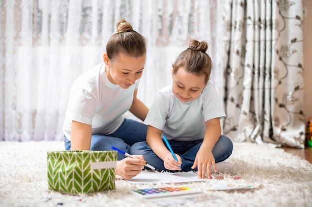 A mãe e a filha estão brincando juntas em casa no chão. feliz e sorridente