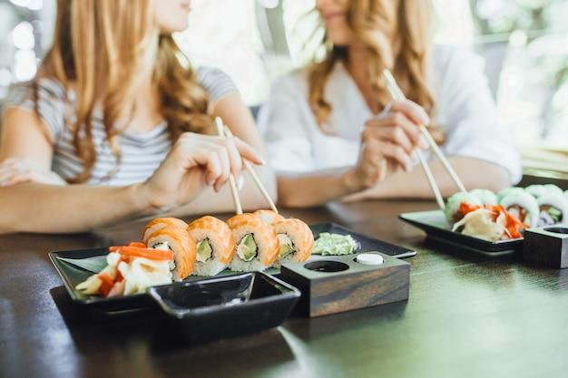 A mãe e a filha linda comem sushi com palitos chineses