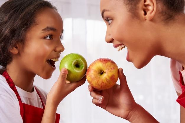 A mãe e a filha nos aventais comem maçãs na cozinha.