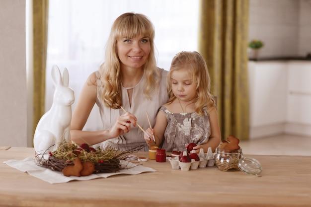 A mãe e a filha pintam ovos da páscoa na sala na tabela do feriado.