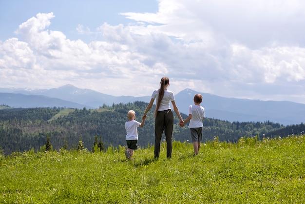 A mãe e dois filhos pequenos estão de mãos dadas em um campo verde contra a da floresta, as montanhas e o céu com nuvens.