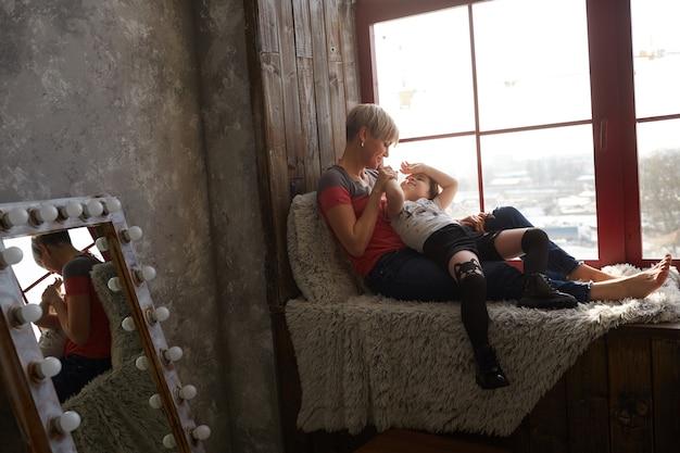 A mãe e filha sentada no parapeito da janela