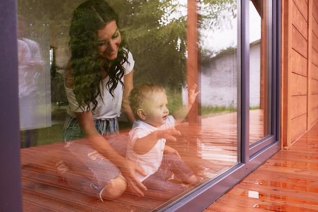 A mãe e filho olhando pela janela