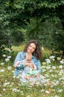 A mãe e o bebê estão sentados em um parque debaixo de uma árvore entre as flores e sorrindo. campo de flores, piquenique ao ar livre.