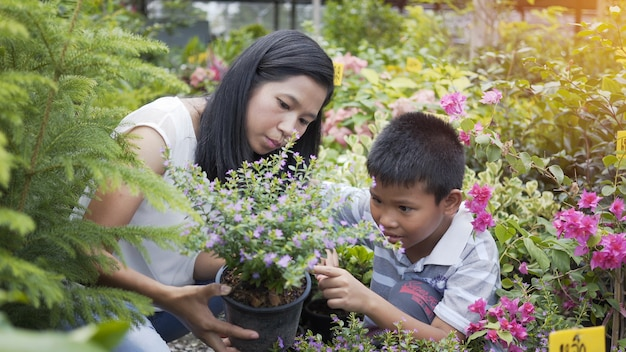 A mãe e o filho asiáticos tomam das árvores no jardim.