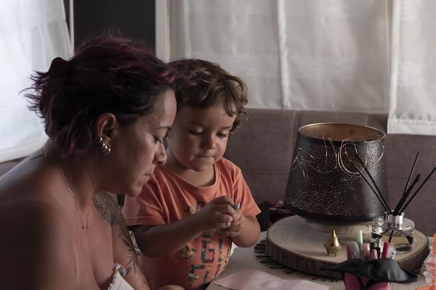 A mãe e o filho de um ano, caucasiano, fazem artesanato em uma caravana durante as férias
