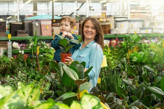 A mãe e o filho dela em uma loja de plantas escolhem plantas. jardinagem na estufa. jardim botânico, cultivo de flores, conceito de indústria hortícola