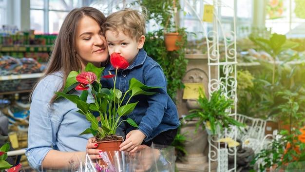 A mãe e o filho dela em uma loja de plantas olhando para uma flor. jardinagem na estufa. jardim botânico, cultivo de flores, conceito de indústria hortícola