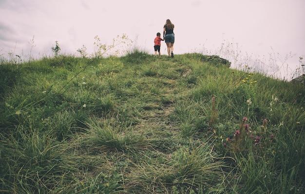 A mãe e o filho estão caminhando na montanha