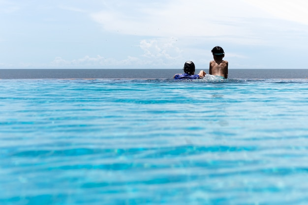A mãe e o filho novo relaxam na piscina que olha sobre o oceano em férias de verão.
