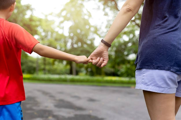 A mãe e o filho que engancha o dedo fazem sua promessa ao andar no parque