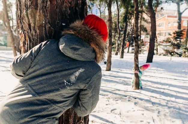 A mãe e o filho se divertem escondendo e procurando em um parque da cidade de inverno, escondendo-se e espiando por trás das árvores