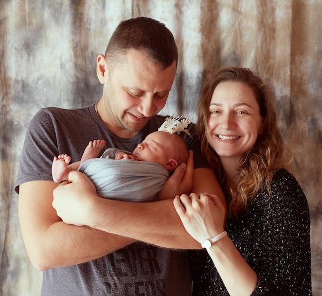 A mãe e o pai abraçando sua filha