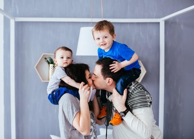 A mãe e o pai beijando e segurando os ombros de seus filhos