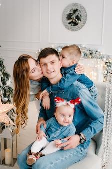 A mãe e o pai seguram o filho e a filha perto da árvore de natal. ano novo. feliz natal.