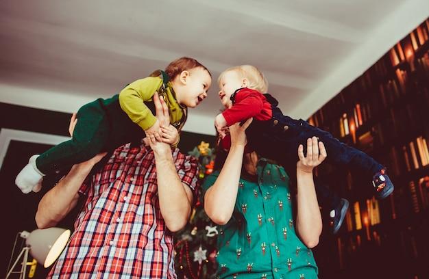 A mãe e o pai tomam as mãos dos filhos