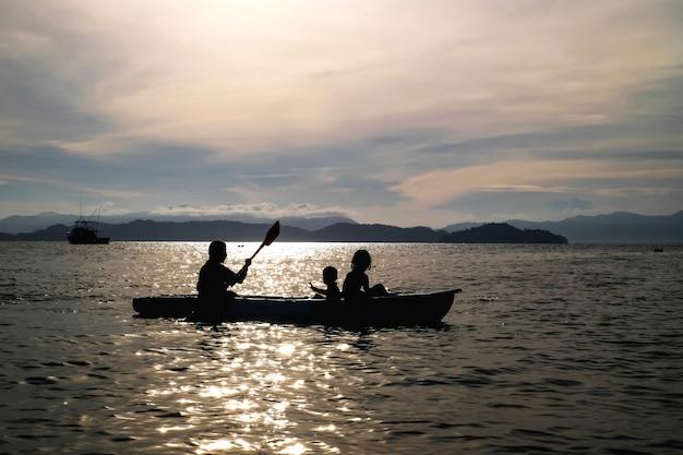 A mãe e os filhos que remam o caiaque no mar no fundo das férias são montanha e por do sol grandes.
