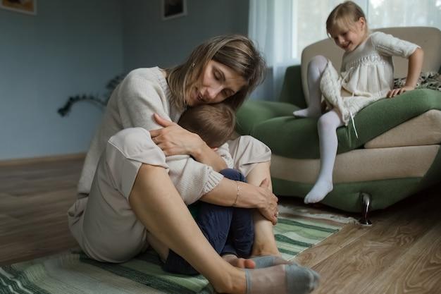 A mãe em casa, sentada no chão, abraça e brinca com as crianças.