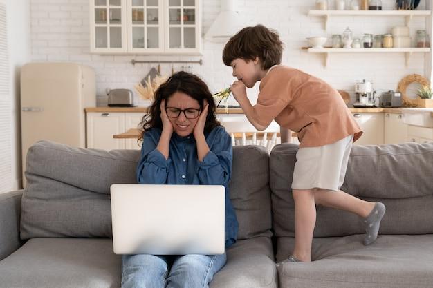 A mãe empresária trabalha em casa, cobre os ouvidos para se proteger de uma criança pré-escolar hiperativa que faz barulho
