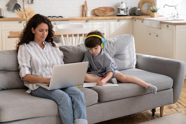 A mãe empresária trabalha online no laptop enquanto o filho pequeno escreve no livro, sentado no sofá em casa