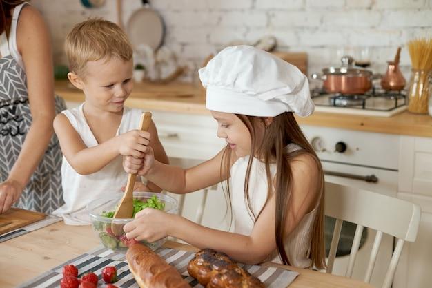 A mãe ensina a filha e o filho a preparar uma salada de legumes frescos