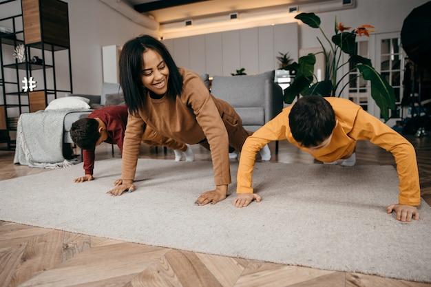 A mãe ensina seus dois filhos a praticarem exercícios físicos esportivos pela manhã em casa. foto de alta qualidade