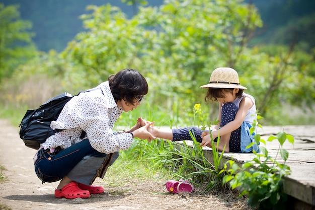 A mãe está cuidando do pé da criança ferida.