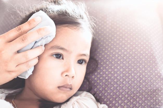 A mãe está esfregando o corpo de criança asiática enferma para reduzir a febre com amor e cuidado