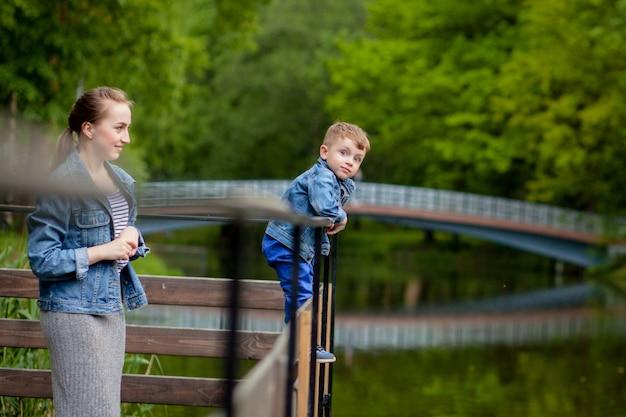A mãe está experimentando que a criança cairá na água. um menino sobe em uma ponte no parque. a ameaça de se afogar. perigo para crianças