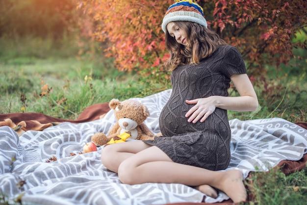 A mãe expectante com uma barriga senta-se em um cobertor e conta histórias para o bebê
