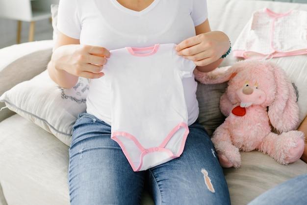 A mãe expectante segura uma roupa branca de bebê com uma cânula rosa nas mãos e uma lebre rosa de pelúcia está sentada ao lado dela