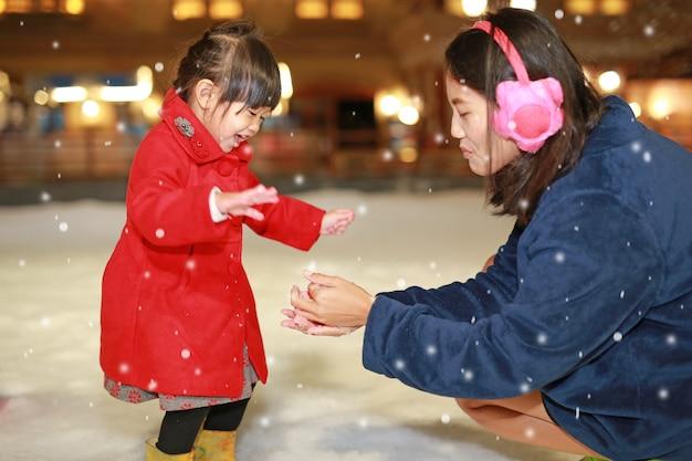 A mãe feliz da família e a menina adorável têm um divertimento na neve, tempo de inverno.
