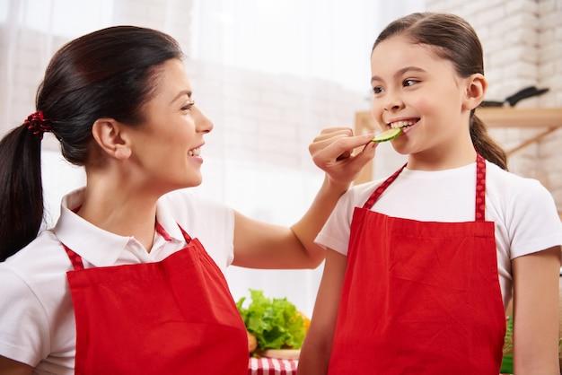 A mãe feliz está alimentando a filha pequena do pepino.