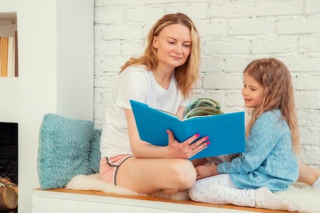 A mãe feliz lê um alegre conto de fadas em um livro para a filha e sorri enquanto está sentada na sala de estar