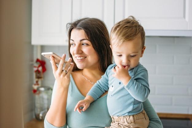A mãe jovem despreocupada com menino nas mãos dita mensagem de voz no celular na cozinha brilhante