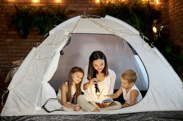 A mãe lê para as crianças uma história para dormir, sentada em uma barraca em casa. mãe, filho e filha se abraçam e leem um livro com uma lanterna nas mãos